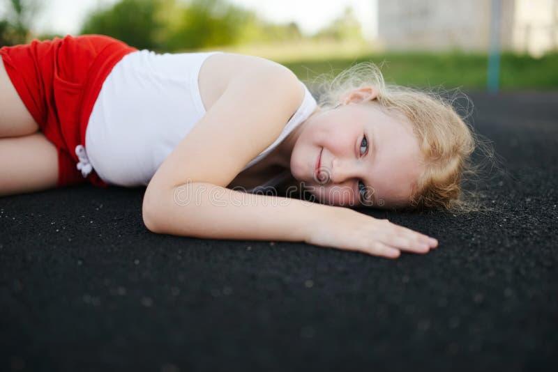 说谎在地板上的女孩户外 免版税库存照片
