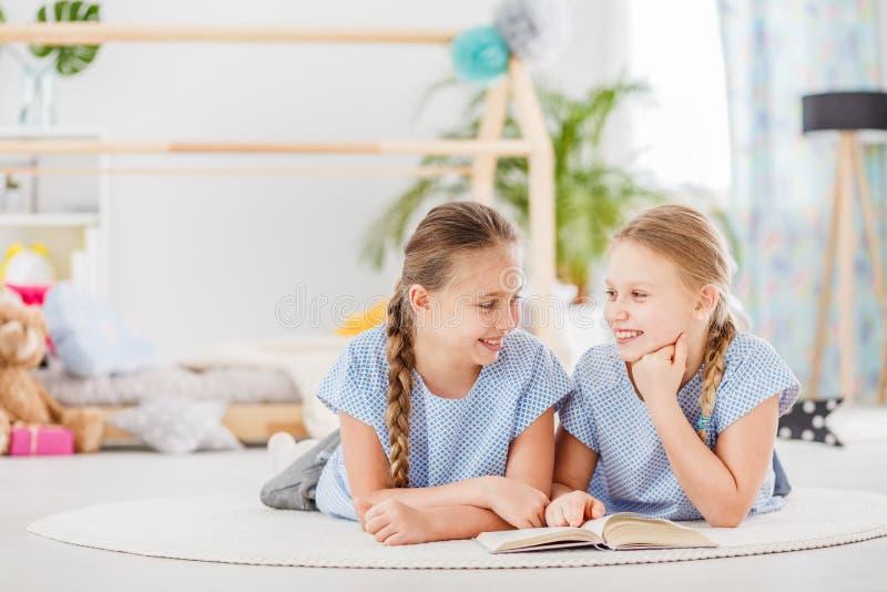 说谎在地板上的姐妹 免版税库存照片