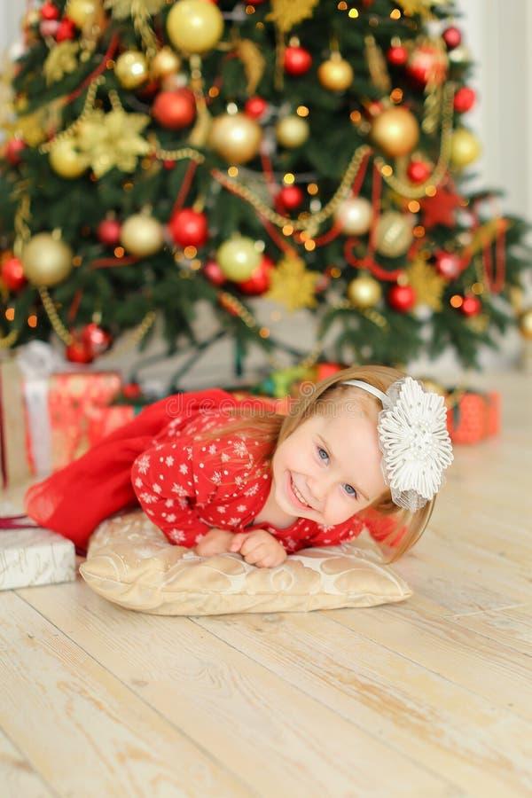 说谎在地板上的小女性女孩在圣诞树和逗人喜爱的礼物附近 免版税图库摄影