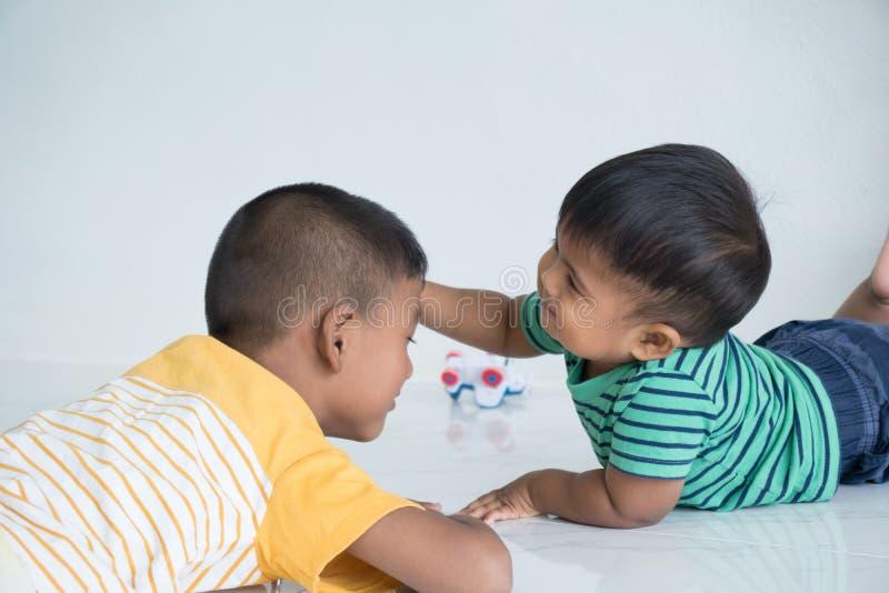 说谎在地板上的逗人喜爱的两兄弟 库存照片