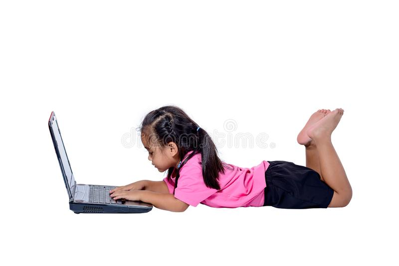 说谎在地板上的逗人喜爱的矮小的亚裔女孩孩子学习或使用在白色背景隔绝的膝上型计算机 免版税库存图片