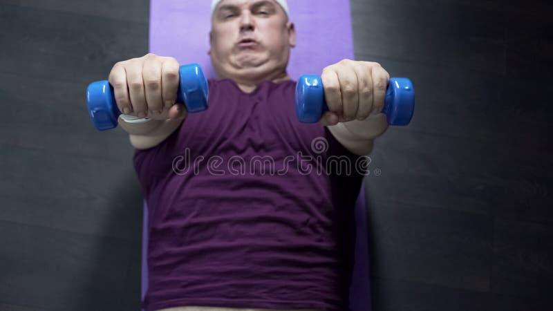 说谎在地板和举的哑铃上的超重人顶视图用努力 库存照片