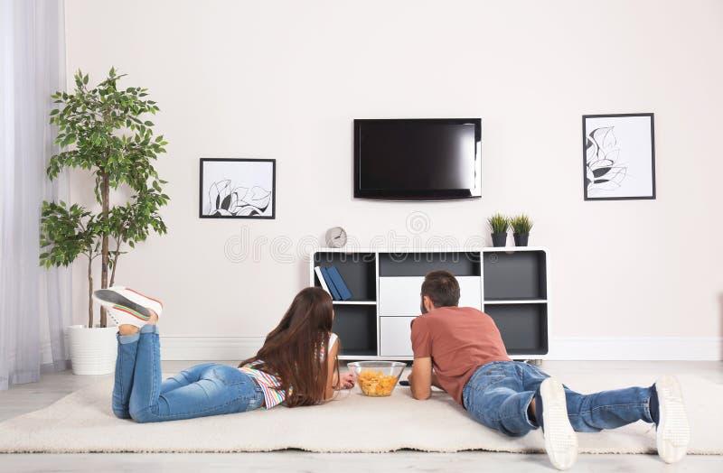 说谎在地毯和看着电视的年轻夫妇 免版税图库摄影