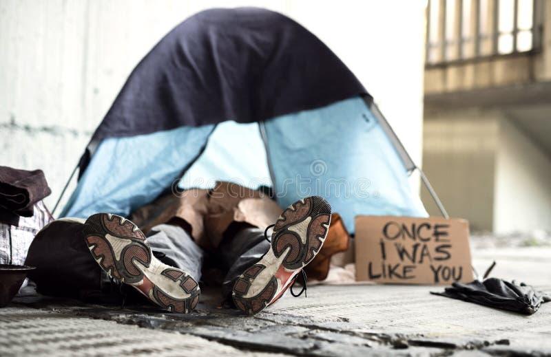 说谎在地面上的无家可归的叫化子人的腿和脚在城市,睡觉在帐篷 免版税图库摄影