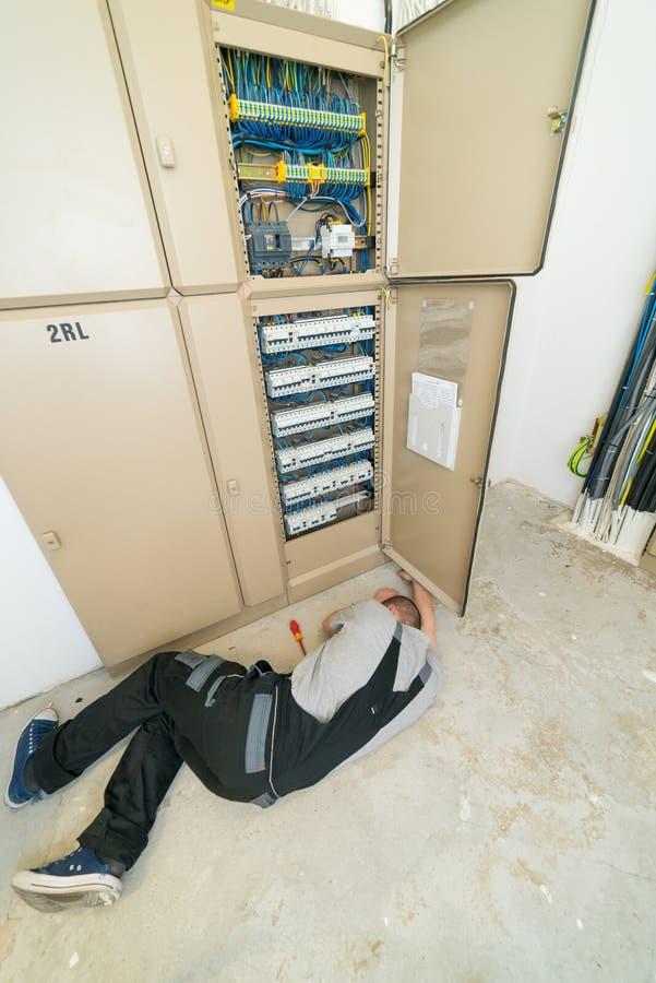 说谎在地面上的电工 免版税库存图片