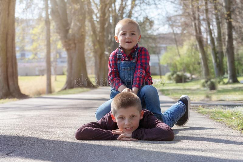 说谎在地面在公园和看照相机的愉快的兄弟画象  免版税库存照片