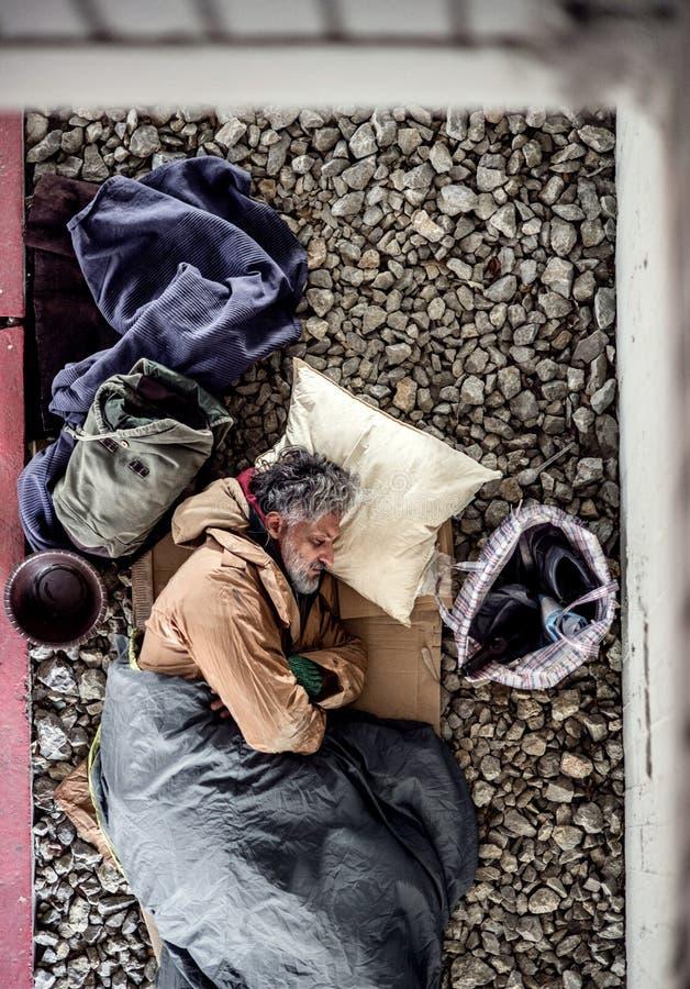 说谎在地面户外的无家可归的叫化子人一张顶视图在城市,睡觉 免版税库存图片