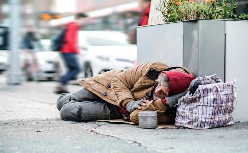 说谎在地面户外的无家可归的叫化子人在城市请求金钱捐赠 免版税库存照片
