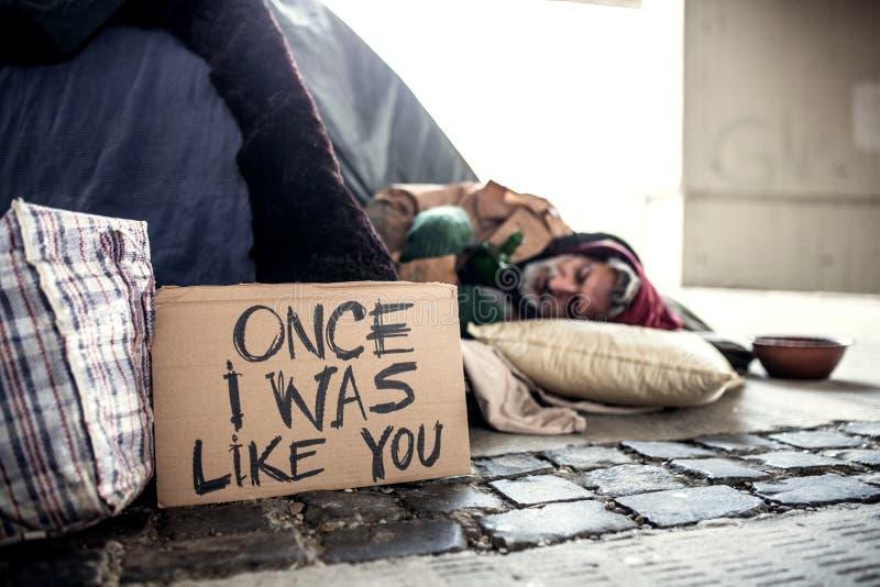 说谎在地面户外的无家可归的叫化子人在城市,睡觉 免版税库存图片