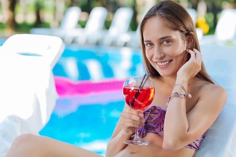 说谎在太阳下的快乐的少妇在外部水池附近 免版税图库摄影