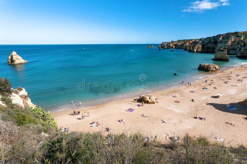 说谎在太阳下的某些人,在葡萄牙的风景海边的宽沙滩 平安和晴朗的区域海洋和海湾  免版税库存图片