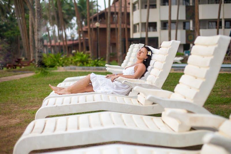 说谎在太阳懒人的白色礼服的美丽的年轻女人由海 旅行和夏天概念 库存图片