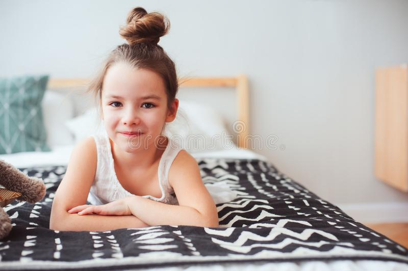 说谎在她的床上的愉快的小孩女孩在早晨,醒在有现代床单的舒适的屋子里 图库摄影