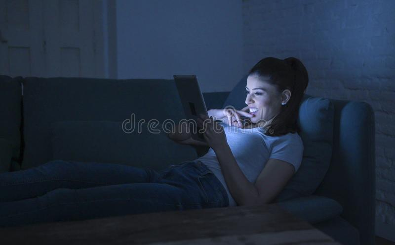 说谎在家庭长沙发的年轻美丽的愉快和轻松的拉丁妇女30s夜间使用数字式设备膝上型计算机片剂垫观看 免版税库存图片