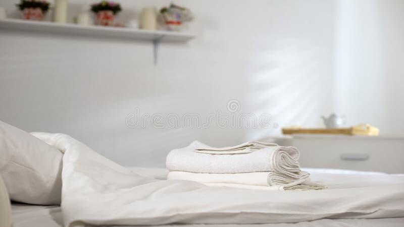 说谎在干净的床上的新鲜的毛巾在酒店房间,芬芳织品软化剂胶凝体 免版税库存照片