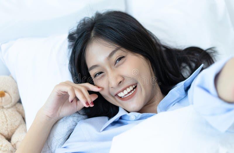 说谎在床上和在家采取selfie的愉快的微笑的年轻亚裔妇女 放松和生活方式概念 库存照片