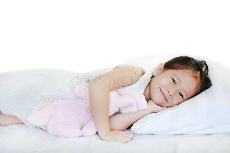 说谎在床上的一个甜微笑的小亚裔女孩的画象与看照相机的早晨 免版税图库摄影