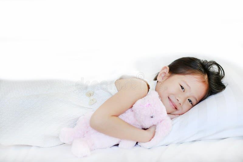 说谎在床上的一个甜微笑的小亚裔女孩的画象与看照相机的早晨 免版税库存照片