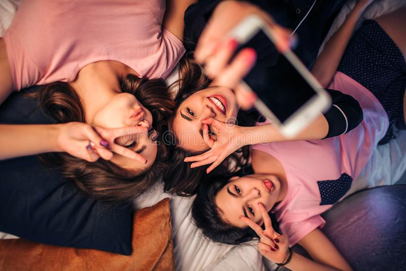 说谎在床上的三嬉戏的年轻女人 他们在照相机摆在并且做不同的姿势 在中间举行白色电话的模型 库存照片