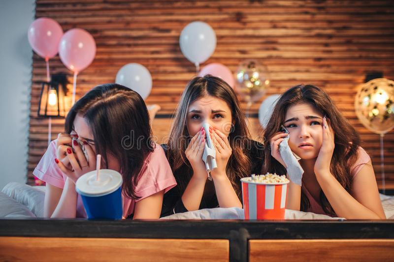 说谎在床上的三年轻女人在欢乐屋子里 他们观看电影和哭喊 女孩在手上拿着白色餐巾 库存图片