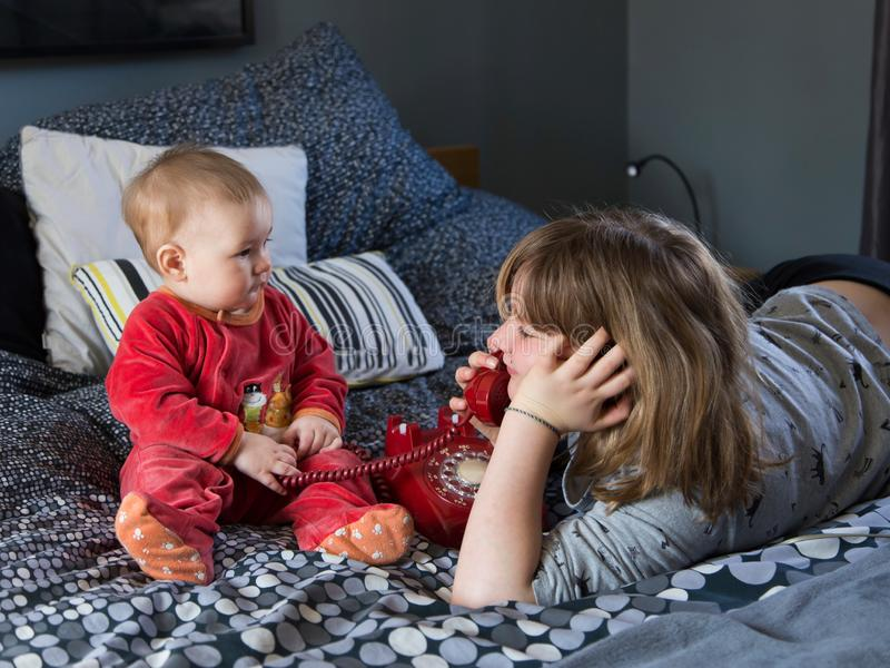 说谎在床上的俏丽的微笑的女孩使用与葡萄酒红色电话和她逗人喜爱的胖的小姐妹 免版税图库摄影