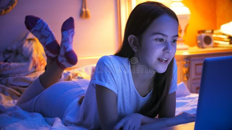 说谎在床上的十几岁的女孩画象在与膝上型计算机的晚上 免版税库存图片
