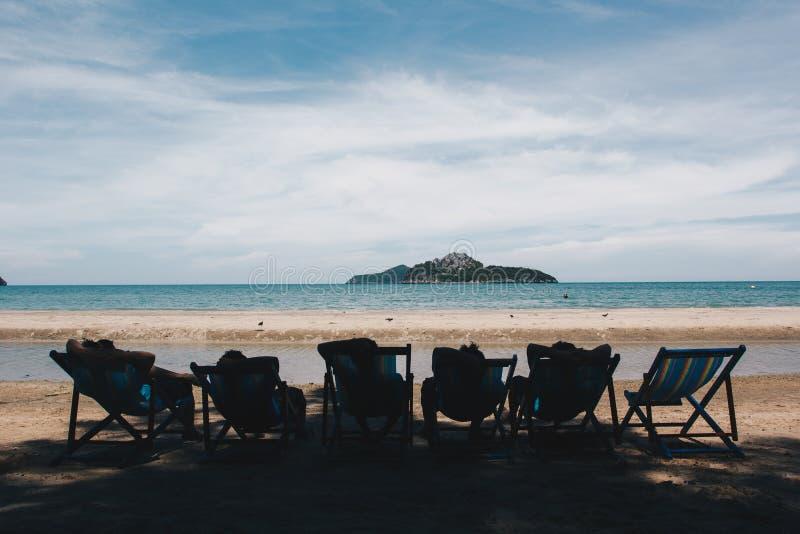 说谎在床上的小组朋友在海滩 免版税库存图片