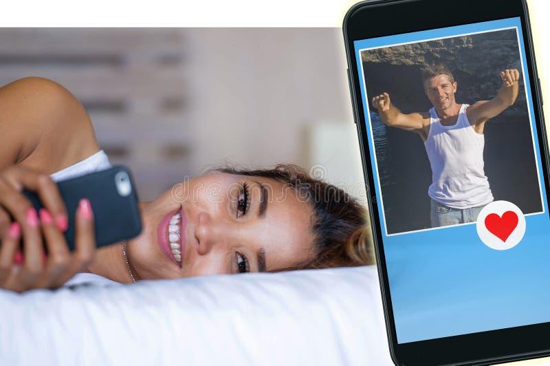 说谎在床上的年轻可爱和愉快的亚裔妇女使用在搜寻人的手机的社会媒介app网上约会送 库存图片