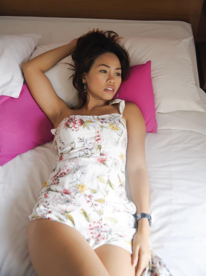 说谎在床上的年轻可爱和美丽的亚裔妇女画象在美好的表示的卧室 库存照片