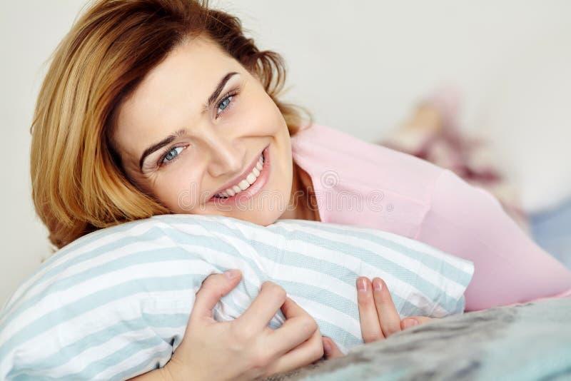 说谎在床上的年轻女人 在家放松的女孩 图库摄影