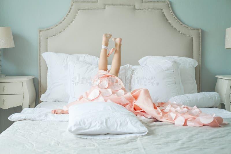 说谎在床上的桃红色礼服的时尚女孩 免版税库存照片