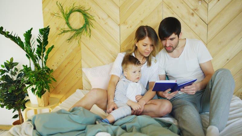 说谎在床上的爱恋的三口之家在早晨 拥抱的家庭和阅读书 免版税库存照片