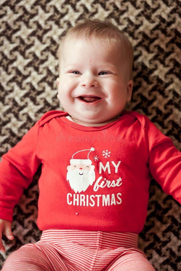说谎在床上的红色套头衫的微笑的男婴 接近的顶视图 库存照片