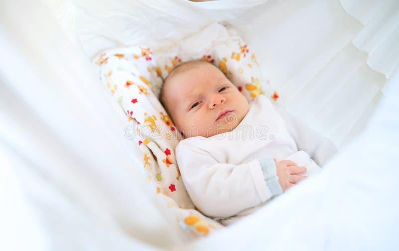 说谎在床上的逗人喜爱的愉快的新出生的婴孩 免版税库存照片