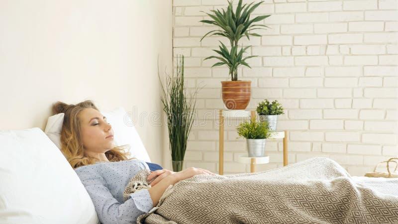 说谎在床的好白肤金发的女孩在有盆栽植物的轻的卧室 免版税库存照片
