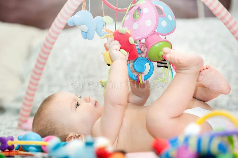 说谎在开发的地毯的婴孩 使用在机动性 r 爬行和使用与在地毯的玩具的甜孩子 图库摄影