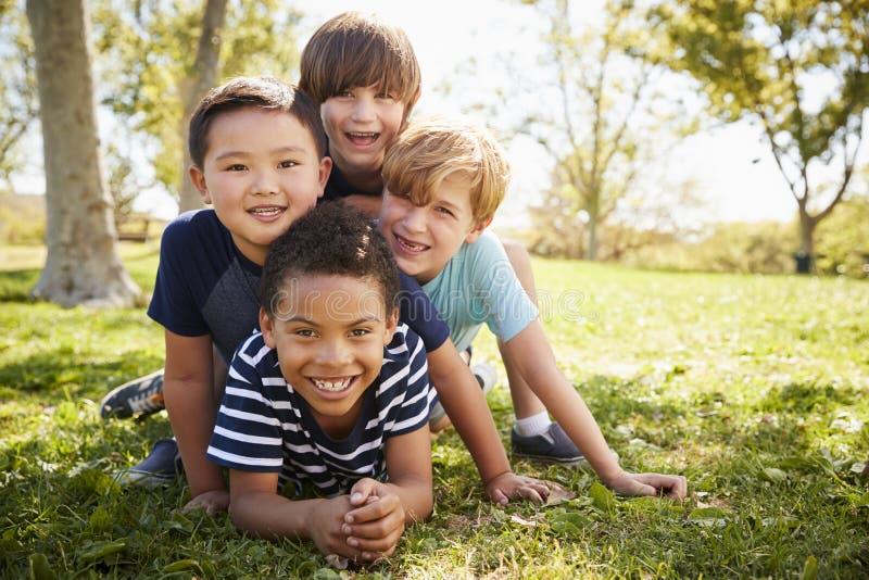 说谎在彼此的四位男小学生在领域,画象 免版税图库摄影