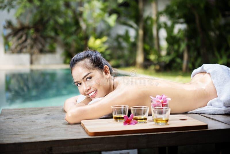 说谎在按摩桌和放松上的美丽的亚裔妇女 图库摄影