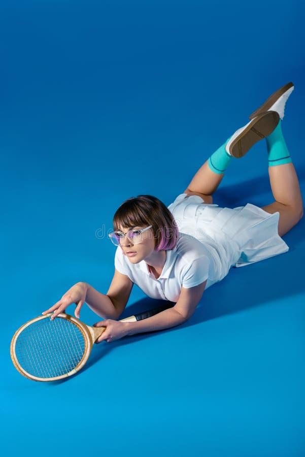 说谎在有网球拍的腹部的诱人的女性网球员 库存照片