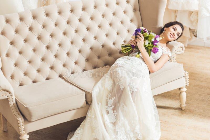 说谎在有花花束的沙发的年轻新娘 图库摄影