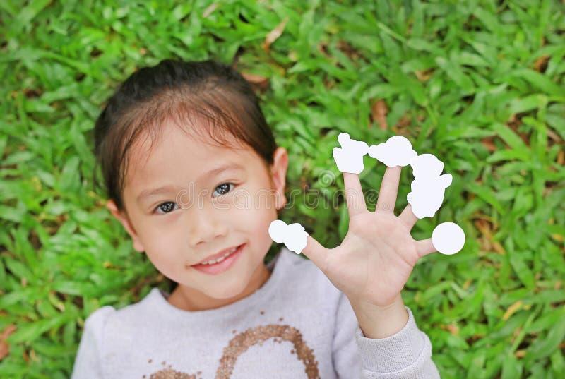 说谎在有陈列空的白色贴纸的绿草草坪的逗人喜爱的矮小的亚裔孩子女孩在她的手指 焦点在手边 图库摄影