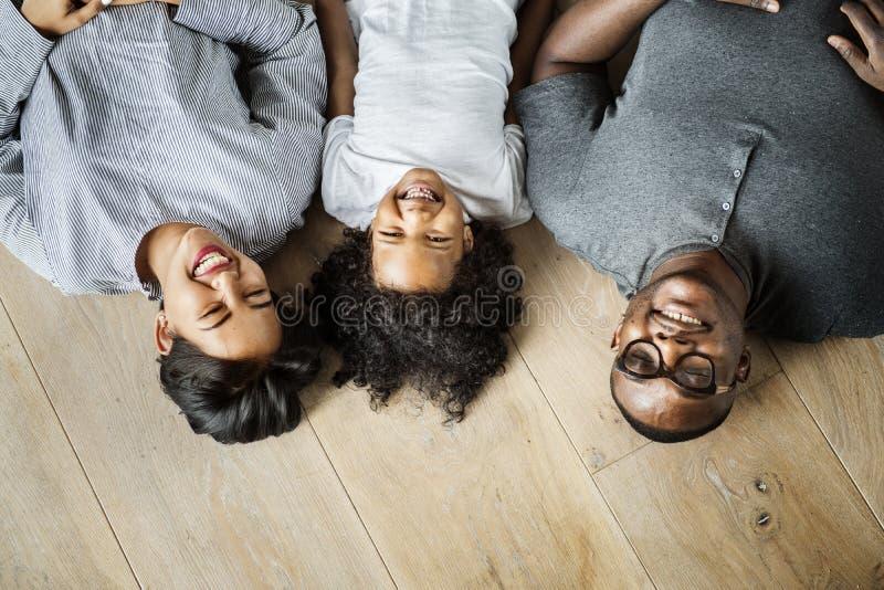 说谎在木地板设计空间的黑家庭 免版税图库摄影
