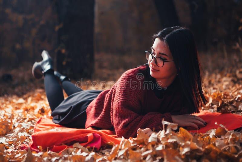 说谎在格子花呢披肩的女孩在秋天森林,自然背景里 图库摄影