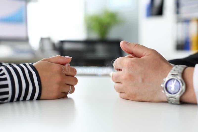 说谎在桌沟通的反面的男性和女性胳膊 库存照片
