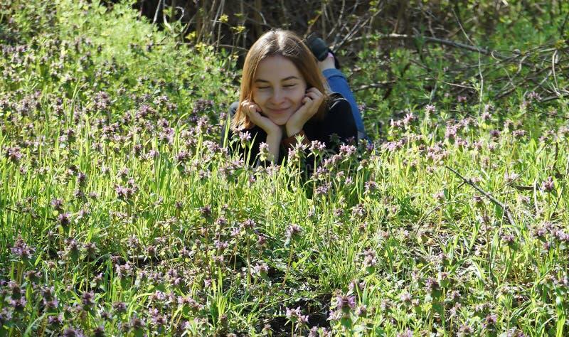 说谎在森林边缘的美丽的少女,居住与自然 库存图片