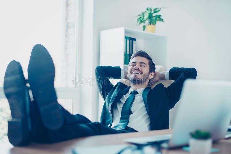 说谎在椅子wi的愉快的快乐的微笑的年轻企业家 库存照片