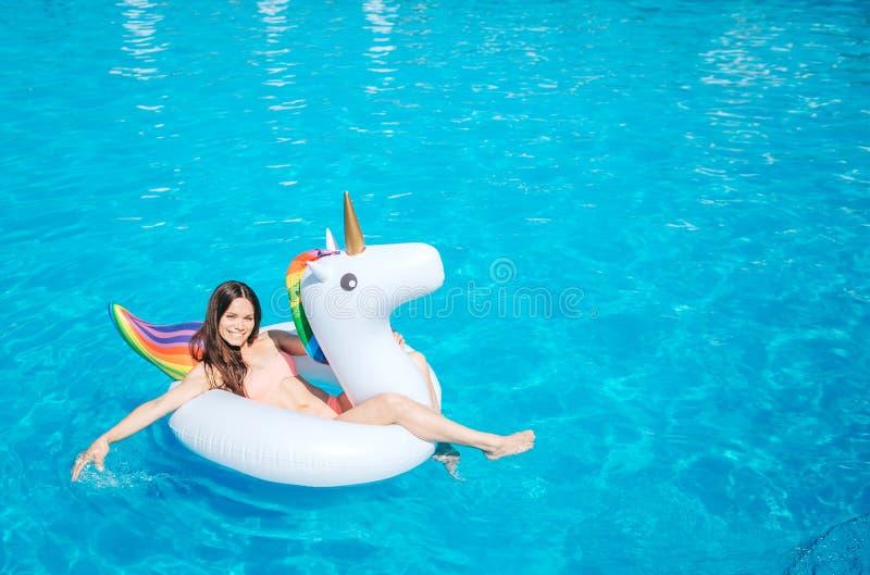 说谎在气垫和感人的水的女孩的图片在游泳池用她的手 她获得很多乐趣 女孩 免版税库存照片
