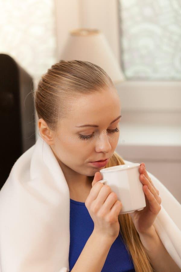 说谎在沙发的妇女在一揽子饮用的茶下 库存照片