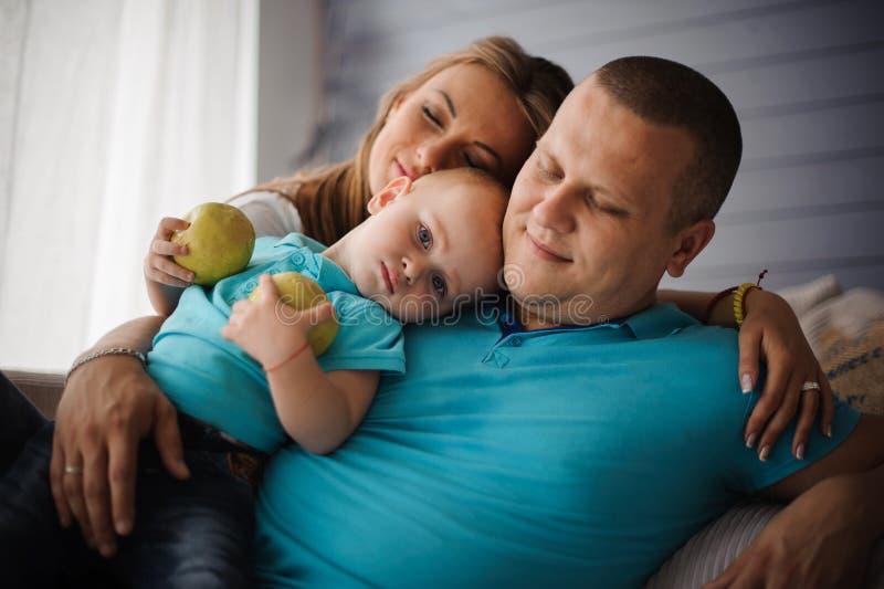 说谎在沙发的父亲、母亲和他们的小儿子 库存图片