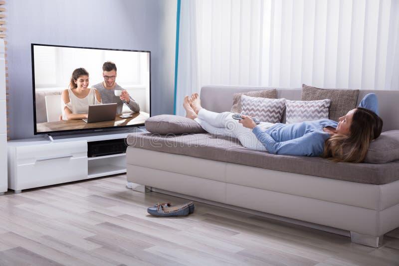 说谎在沙发观看的电视上的妇女 免版税库存照片
